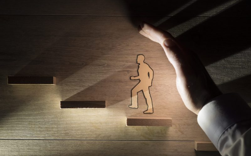 Conceptual close-up of the hand of a man protecting a paper man during progress while climbing stairs against wooden background for copy space.
